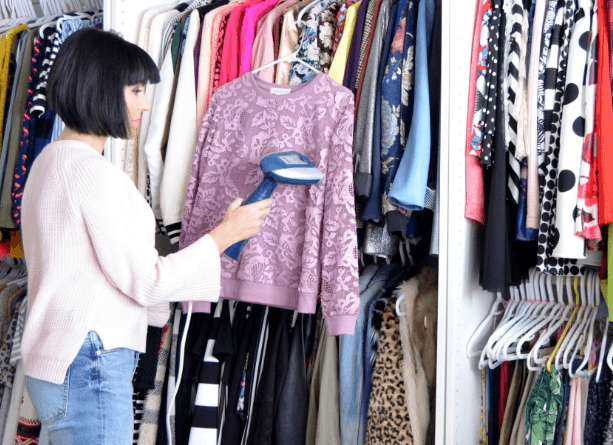 a lady using garment steamer on her clothes