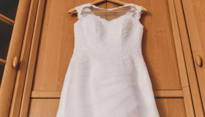 wedding dress hanging on hanger in room