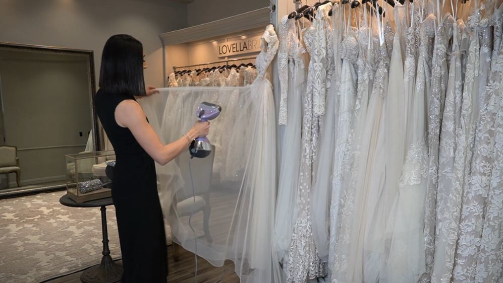 a woman is steaming wedding dress